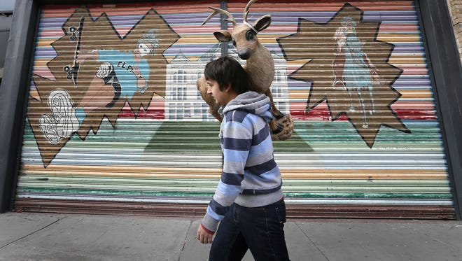 John Bahena, of Juarez, carries a deer statue to his vehicle on El Paso Street in December 2017 as he shopped with family along the famed downtown El Paso shopping district. El Paso Street has long been know for its interesting finds and great deals, luring shoppers from Juarez and El Paso.