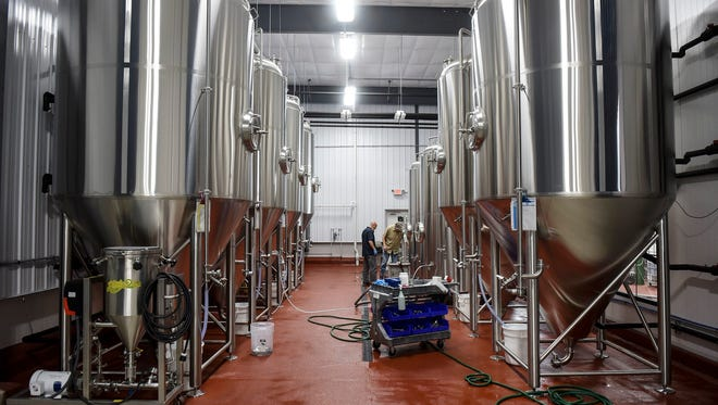 Brewers check on batches of beer May 24, 2017, at the Beaver Island Brewing's new production facility in St. Cloud.