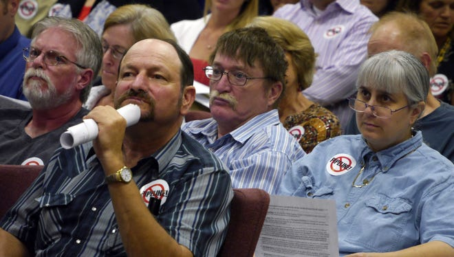In this photo taken on Aug. 13, 2014, Page Graves, of Raphine, Va., listens with other citizens to a representatives from Dominion present their proposal for a natural gas pipeline that would run through Augusta County to the Augusta County supervisors in Verona, Va.