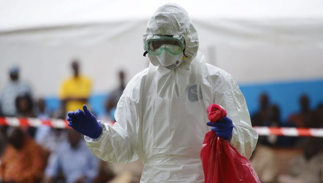 A man prepares to take off his protective suit at Biankouma hospital, Ivory Coast, during a simulation on Aug. 14.