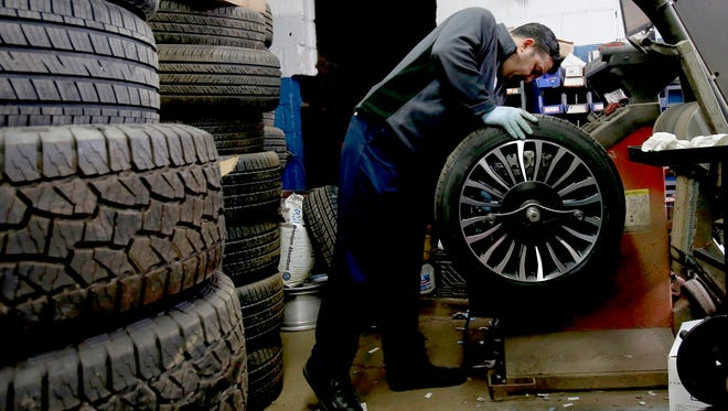 Veli Talybov, 48 of Oak Park and a tire technician, works on balancing a tire at Wetmore's Tire and Auto in Ferndale on Wednesday, April 4, 2018.