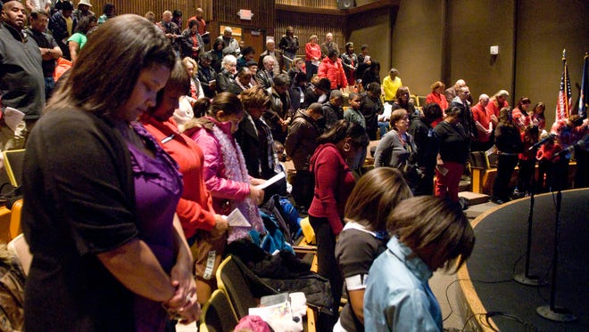 Audience members pray during a Martin Luther King Jr. Day event in 2013 at St. Clair County Community College.
