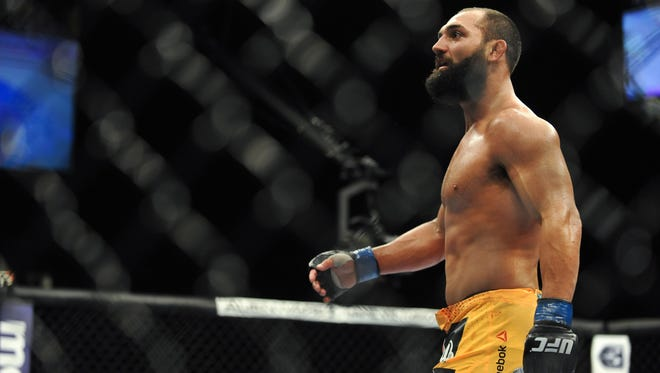 Johny Hendricks (blue gloves) looks on between rounds of his welterweight championship bout during UFC 167 at MGM Grand Garden Arena.