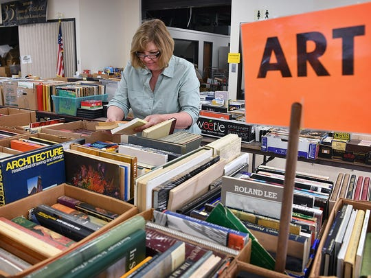 Ronda Hare sorts some of the 100,000 donated books for sale at the Midwestern State University Sikes Lake Center for the 18th Annual Book Fair for the Wichita Adult Literacy Council.