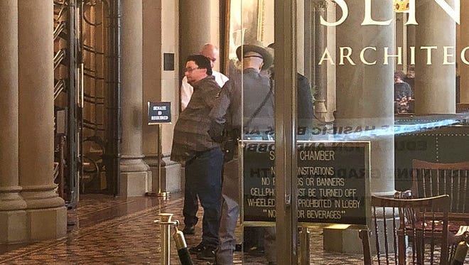 This photo provided by Sean Ewart shows New York Daily News reporter Ken Lovett being handcuffed and taken into custody by state police after a Senate sergeant-at-arms observed him speaking on his cellphone in the lobby, outside the Senate chambers in the state Capitol, Albany, N.Y., Wednesday, March 28, 2018. (Sean Ewart via AP)