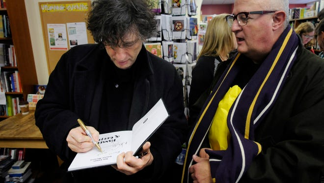 Author Neil Gaiman, left, signed one of his works at Oblong Books &; Music on Saturday.