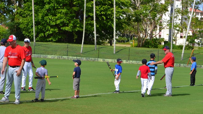 In this photo provided by the Guam Baseball Academy, coaches work with young ballplayers to improve their baseball skills.