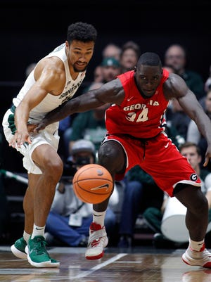 Michigan State's Kenny Goins, left, and Georgia's Derek Ogbeide chase the ball during the first half of MSU's 80-68 exhibition win over Georgia on Sunday in Grand Rapids.