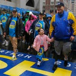 2013 Boston Marathon bombing survivors Paul (C) and J.P. Norden (R) cross the finish line on the one-year anniversary of the bombings in Boston, Massachusetts April 15, 2014.