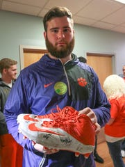 Clemson football player Sean Pollard holds his size 15 shoes he and other players signed for one-year old Hudson Belviso of Spartanburg on Thursday at the Shriners Hospitals for Children in Greenville. Pollard donated the shoes he wore in the National Championship game in Tampa.