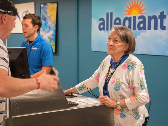 Helena Redmon, an agent with Allegiant Air, helps a