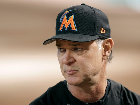 FILE - In this Sept. 22, 2017, file photo, Miami Marlins manager Don Mattingly looks on during batting practice before a baseball game against the Arizona Diamondbacks, in Phoenix. The Marlins are likely in for another long season, but spring training should actually be interesting as Mattingly sorts out the numerous prospects acquired in payroll-slashing trades by new CEO Derek Jeter. (AP Photo/Ralph Freso, File)