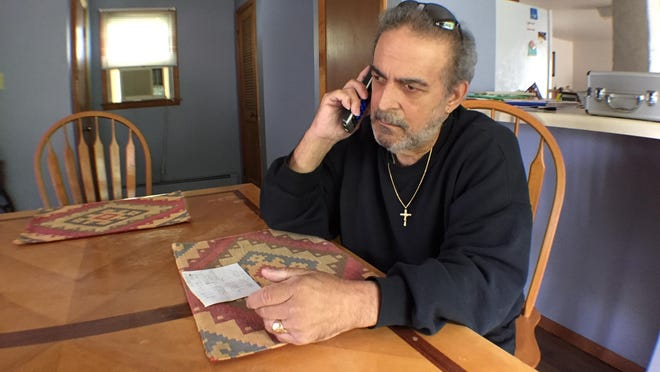 Stafford resident Philip Morales talks on the telephone with Speeddate.com about an unauthorized charge.