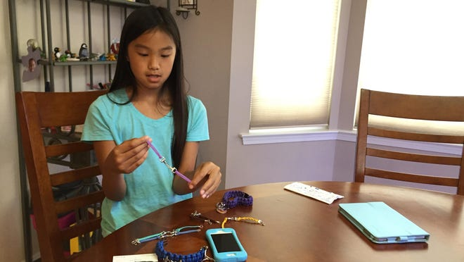 Lizzie Chan shows some of the bracelets she makes for her small business, Equine Creation.