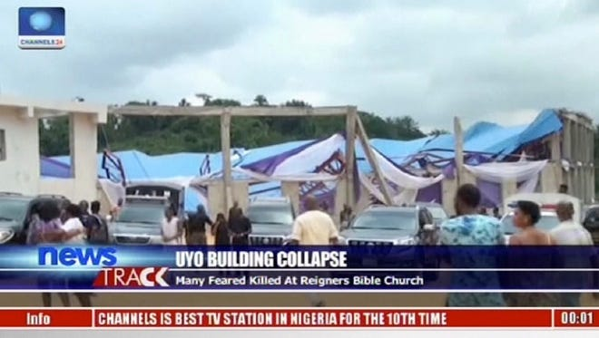In this image taken from video people stand at the scene after the roof of The Reigners Bible Church International collapsed onto worshippers in Uyo, southern Nigeria on Saturday, Dec. 10, 2016, killing dozens, witnesses and an official said.