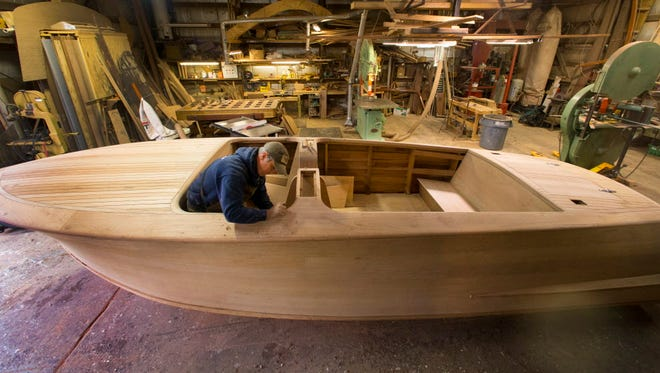 Lars Bergersen hand planes a rounded corner of a 22-foot Shepherd boat Thursday at  Bergersen Boat Co. in Springfield. The vessel, which will take about a year to complete, is made of Philippine mahogany, white oak, Douglas fir and marine fir plywood with about 8,000 silicon bronze screws as fasteners.