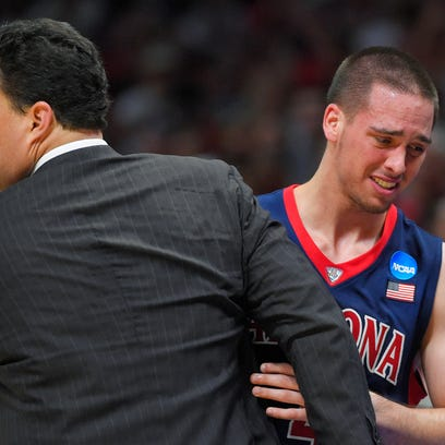 Arizona guard T.J. McConnell hugs head coach Sean Miller