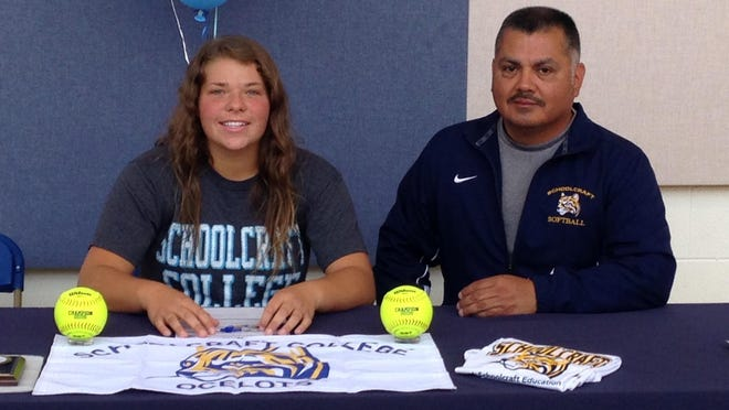 Waterford Mott catcher Rebekah Mathers and Schoolcraft softball coach Rey Linares celebrate after Mathers signed to play for the Ocelots in their debut season.