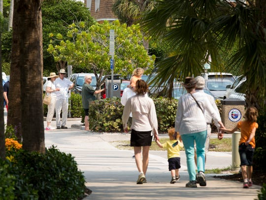 Residents and tourists alike use the parking lots near the Naples Beach Pier on Monday, March 6, 2017.