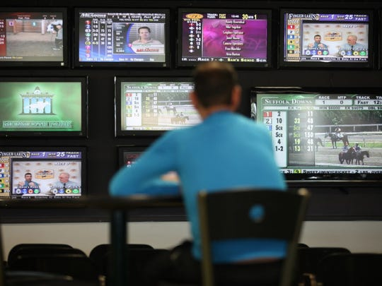 Monitors at Monmouth Park in Oceanport showing races from other tracks, seen in 2014. New Jersey has been fighting to get Vegas-style sports gambling at such venues.