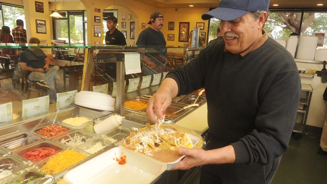 Owner Pablo Garcia whips up an order of chilequiles at the Burrito Express restaurant in Oxnard.