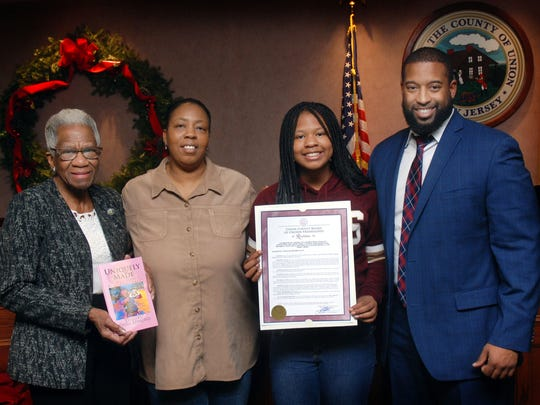 """Union County Freeholders Vernell Wright and Mohamed S. Jalloh present a resolution to Dasia """"DasiaVu"""" Edmond of Union congratulating her on officially publishing two books. They were joined by her mother, Belinda Salley. The 12-year-old Burnet Middle School student released """"Uniquely Made: 'Girls Don't Play Football'"""" in 2016 and """"Hair Chronicles: 'The Struggles of Natural Hair'"""" this summer. The books are available on www.amazon.com."""