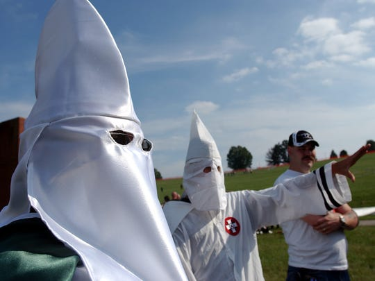 Members of the Ku Klux Klan participate in a rally