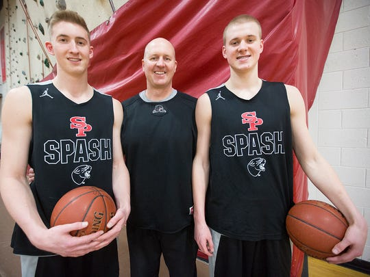 Assistant coach Dave Hauser, center, with his sons Sam Hauser, left, and Joey Hauser, right, during basketball practice at Stevens Point Area Senior High School, Wednesday, March 9, 2016.