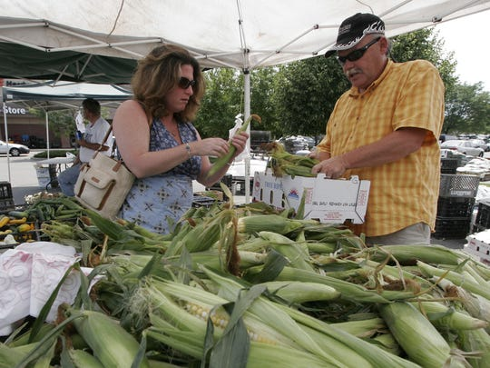 David and Fran Crown fill a box with corn at other veggies at the Fort Collins Farmers' Market.