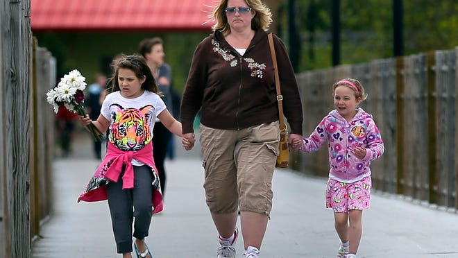 Heather, (left) Christy and Caitlyn Betley walk the Trestle Trail on Tuesday as they carry flowers to a memorial in the pavilion near Fritse Park in the Town of Menasha.