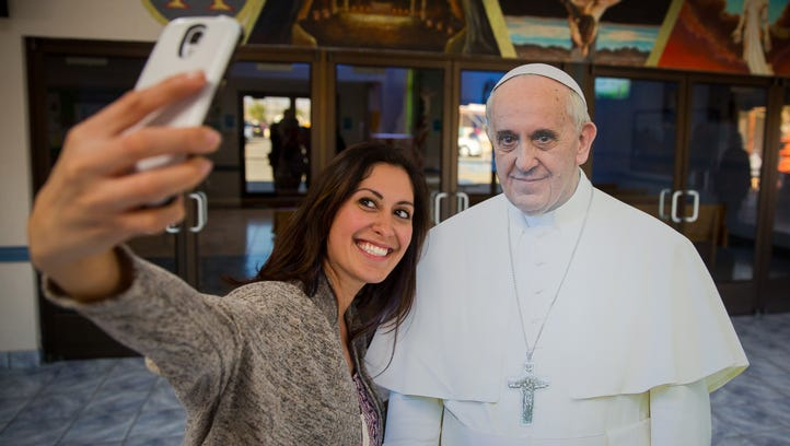 Desarae Diaz takes a selfie with a cardboard cutout of Pope Francis in the foyer of Holy Cross Catholic Church. According to youth minister Craig Bullock everyone who comes into the foyer has taken a photo of the cutout.