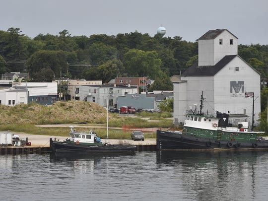 View of the site for redevelopment and the granary, right, with tug boats docked at the waterfront. Meetings and events to solicit public opinion find respondents want to integrate working waterfront with tugs remaining at the site. The photo was taken Aug. 6, 2017. Funds are being donated to the city to move the granary back to the site, which requires approval of the state Board of Commissioners of Public Lands.