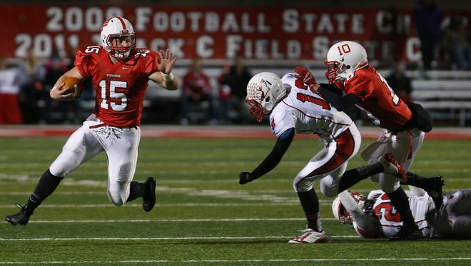 Center Grove running back Max Norris puts distance between him and Southport's Justin Herring as he takes too from midfield on a 50-yard run resulting in the Trojan's second touchdown, regaining their lead in the first half, 14-10, during their regional showdownat Center Grove on Friday, Nov. 7, 2014. Trojan teammate Jade Doyle, No. 10, defends against Herring and Darius Bryant, on ground.