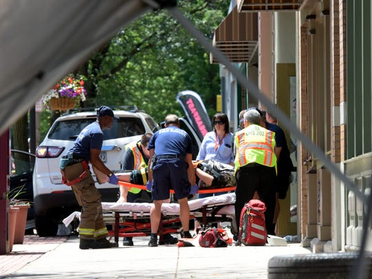Emergency workers lift an injured pedestrian onto a