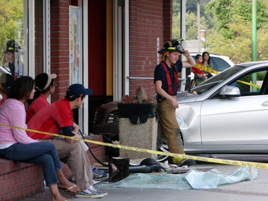 Employees watch as New York State police and Goldens Bridge firefighters work to clear a car that crashed into the Dunkin Donuts / Baskin Robbins in the Goldens Bridge shopping center at Routes 138 and 22 in Goldens Bridge Aug. 6,  2010. ( Frank Becerra Jr  / The Journal News )