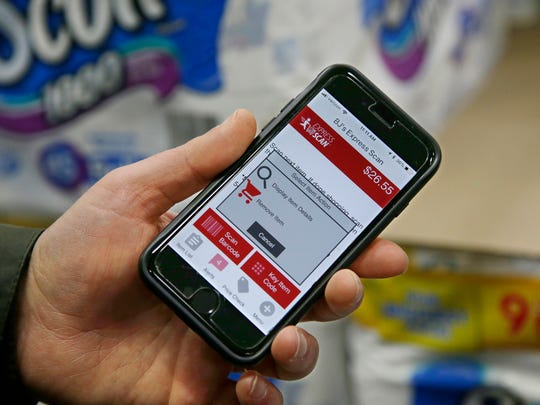 Tony D'Angelo holds up his phone, which displays an option to remove an item from his shopping cart on his BJ's Express Scan app, while shopping at the BJ's Wholesale Club in Northborough, Mass. The technology allows shoppers to scan UPC codes on items as they shop. It can be used for lots of products beyond just groceries, and people change their minds about something, they can delete items and change quantities before they check out.