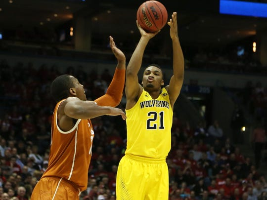 Michigan's Zak Irvin (21) scores against Texas Jonathan Holmes during second-half action in the third round of the NCAA Men's Basketball Tournament at BMO Harris Bradley Center in Milwaukee Wis., Saturday, March 22, 2014. Michigan defeated Texas, 79-65.)