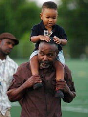 Tyrone Todd of Farmington Hills carries Nelson Livas, 2, on his shoulder during the march.