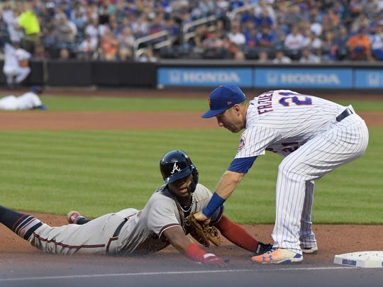 New York Mets third baseman Todd Frazier, right, tags out Atlanta Braves' Ronald Acuna Jr. to complete a double play to end the top of the third inning of a baseball game Friday, Aug. 3, 2018 in New York.