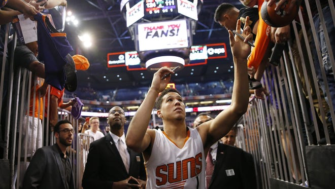 Phoenix Suns guard Devin Booker (1) signs autographs for fans after beating the Dallas Mavericks 124-111 in their final home game of the season at Talking Stick Resort Arena in Phoenix, Ariz. April 9, 2017.