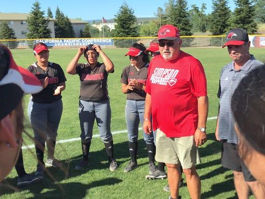 Simpson head softball coach Wayne Stower talks to players