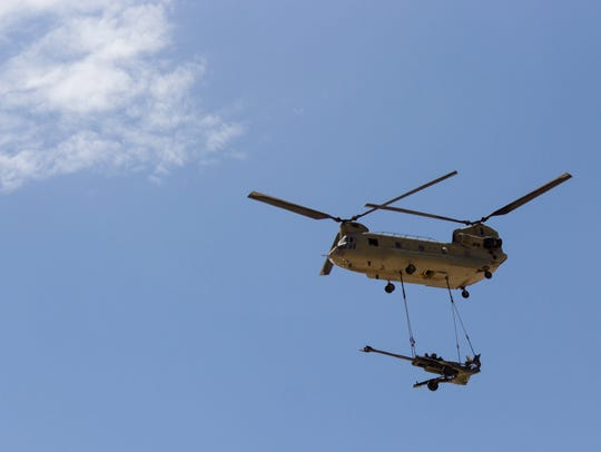 A Chinook helicopter sling loads a howitzer during