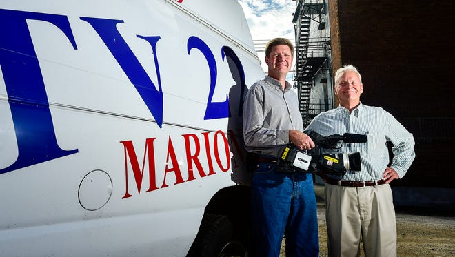 Mark Hiner and Mike Zucker pose for a portrait by their news van. Hines and Zucker recently purchased TV 22, a local TV station based in Marion. The station covers football and other news around Marion, as well as broadcasting network television reruns.