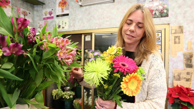 MariEllyn Dykstra Donnellan of A. Dykstra Florist and Greenhouse in Chestnut Ridge puts together a bouquet of flowers on Wednesday, Dec. 16, 2015.