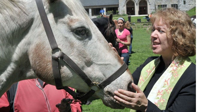 Former Wilson College Chaplain the Rev. Rose Magee says a prayer for a horse during a past Blessing of the Animals. All types of animals are welcome at the event.