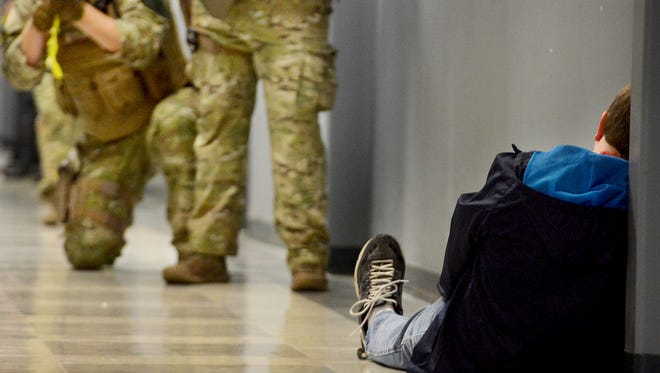 KENNETH CUMMINGS/The Jackson Sun A student-actor sits ?injured? inside a hallway at Jackson State Community College as Madison County SWAT officers work to clear a floor Monday during an active shooter training simulation. A student sits injured inside a hallway at Jackson State Community College as Madison County SWAT officers work to clear a floor Monday during an active shooter training simulation.