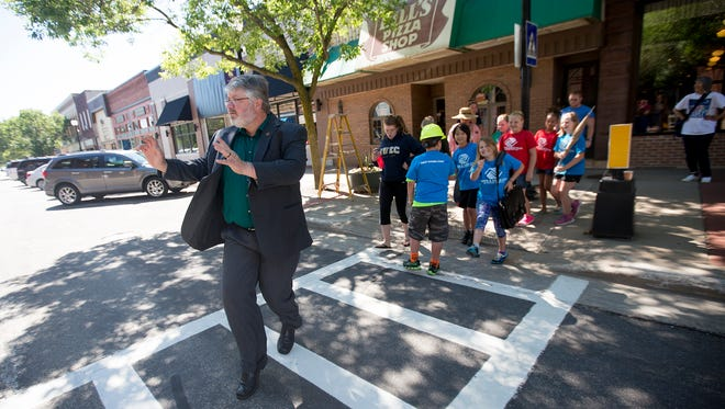 Mayor Mike Wiza does a silly walk down the Creative Crosswalk in downtown Stevens Point, Wednesday, June 29, 2016. The Creative Crosswalk encourages pedestrians to creatively express themselves as they cross the street.