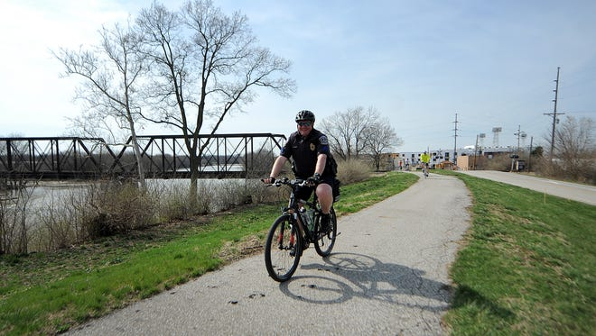 A police officer rode along the White River Trail during then-Mayor Greg Ballard's Spring Fever Bike Ride on April 12, 2014, in Indianapolis.