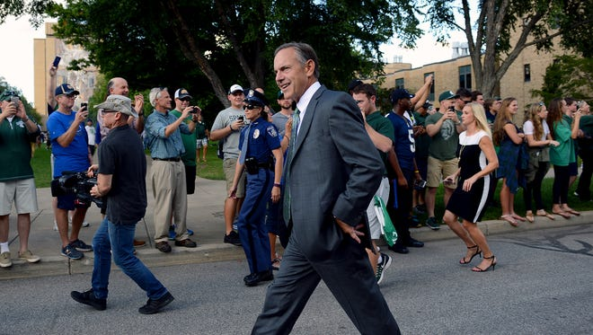 Head coach Mark Dantonio smiles to the crowd after getting off the bus and heading into Notre Dame Stadium before the start of the Spartans game against Notre Dame Saturday, Sept. 17, 2016 in South Bend, Ind.