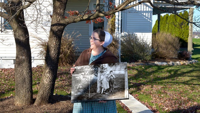 In this Nov. 12, 2016 photo, Alice Reiff Weaver stands in the same spot in Lancaster County, Pa., where photographer LNP photographer Richard Hertzler had taken her photo 40 years before. The metal fence is gone, and the dogwood tree is no longer a mere sapling, but Weaver's open smile has remained unchanged. (Richard Hertzler/LNP via AP)